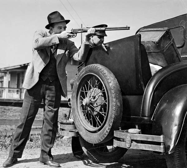 Feb. 17, 1938: Detective Lieutenant Robert Underwood fires into home in the 1700 block of East Twenty-second street as police trade shots with barricaded suspect George Farley. Two deputy city marshals were slain by Farley as they tried to serve eviction notice on him. Los Angeles Times Photographic Archive/UCLA